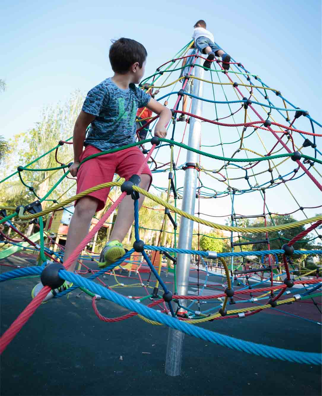 boys playing in a climbing pyramid in children's playgrounds