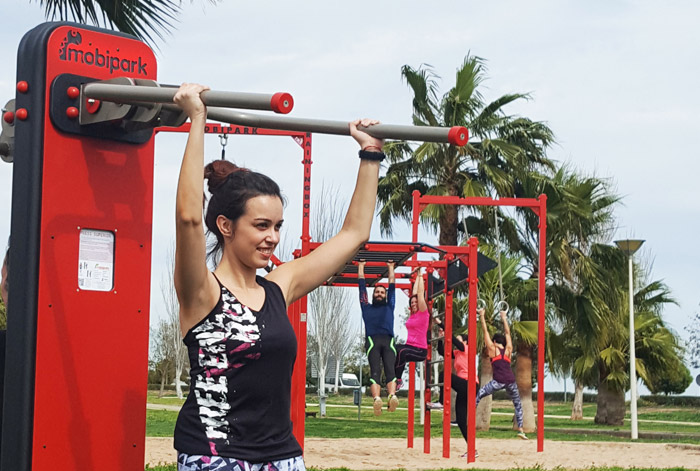 girl doing arm exercise at urban gym and group of people doing Crossfit product ranges exposed at trade fair Tecma 2018